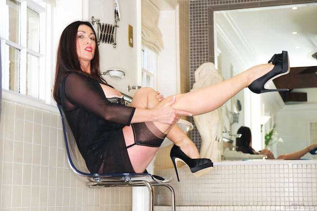Long legs seamed stockings and sexy lingerie Miss hybrid sits astride the see through chair.